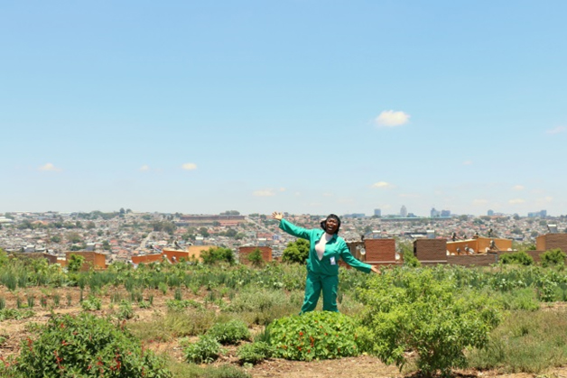 black woman in her green garden