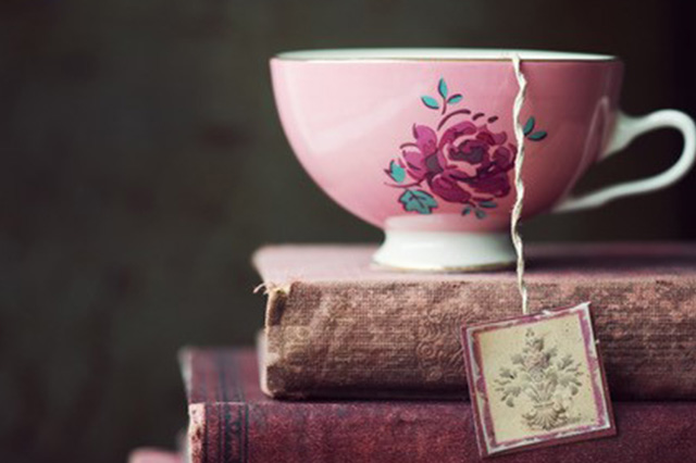 tea in a old pink cup on a stack of books