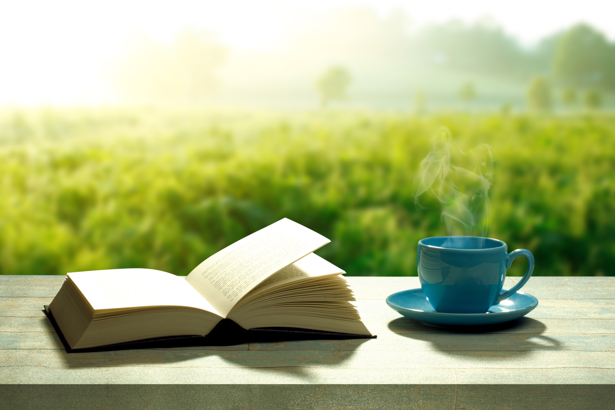 open novel book with a blue coffee cup and a wooden table